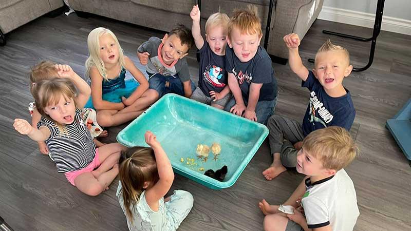 Children gathered around Baby Chicks