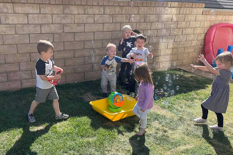 Kids Chasing Bubbles Outdoors
